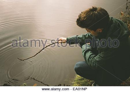 Junger Mann kauert am Ufer machen Wellen im Wasser mit Zweig - Stockfoto