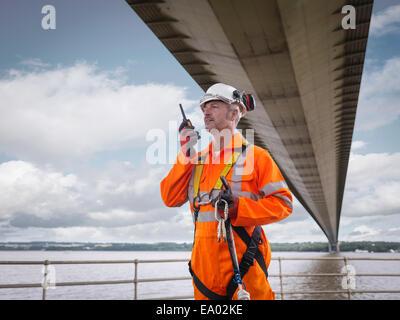 Bridge worker using walkie-talkie under suspension bridge Humber Bridge UK was built in 1981 - Stock Photo