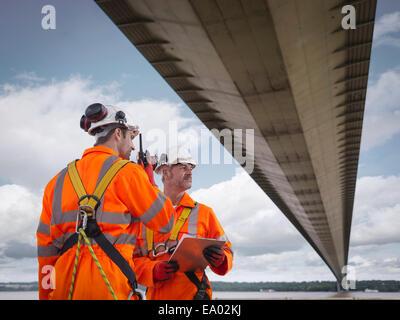 Bridge workers using walkie-talkie under suspension bridge Humber Bridge UK was built in 1981 - Stock Photo