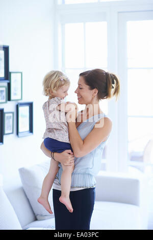 Mid adult woman and toddler daughter in living room - Stock Photo