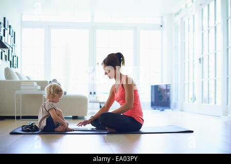 Mid adult mother and toddler daughter practicing yoga in living room - Stock Photo