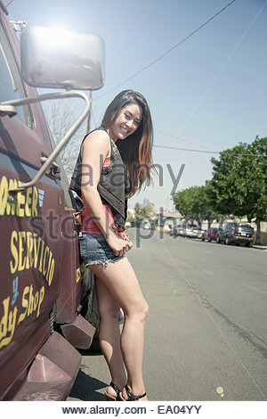 Portrait of young woman, standing beside truck - Stock Photo