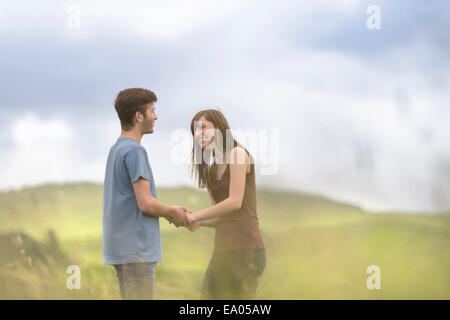 Young couple holding hands together in meadow under bright sky - Stock Photo