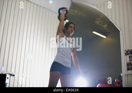 Woman lifting kettlebell in gym - Stock Photo