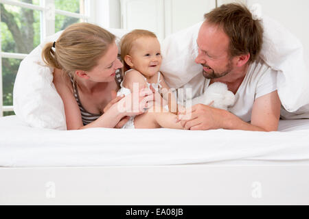 Parents playing with baby daughter under duvet - Stock Photo