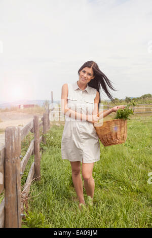 Young woman with basket of vegetable on field, Roznov, Czech Republic - Stock Photo