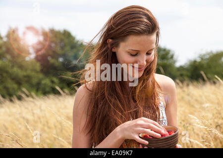 Young woman holding bowl of fresh fruit in field - Stock Photo