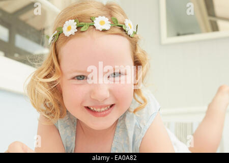 Portrait of girl in daisy chain lying on holiday apartment seat - Stock Photo