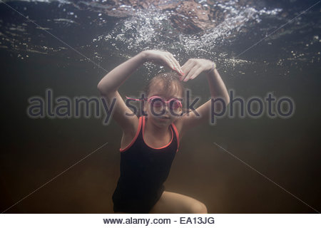 Portrait of girl swimming underwater making heart shape with arms - Stock Photo