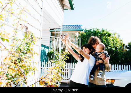 Woman taking family selfie at front of house - Stockfoto