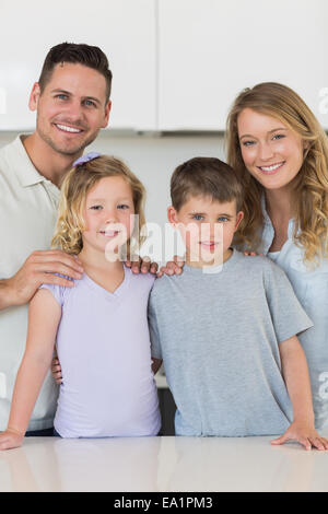 Happy family standing together in kitchen - Stock Photo