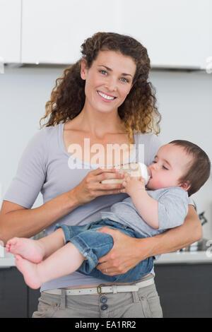 Happy mother feeding milk to baby - Stock Photo