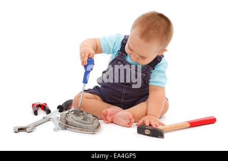 Little baby boy sitting and playing with real tools - Stock Photo