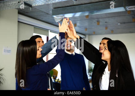 Happy business team is holding hands together. Raising one hand up - Stock Photo