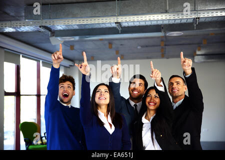 Group of cheerful business people pointing up - Stock Photo