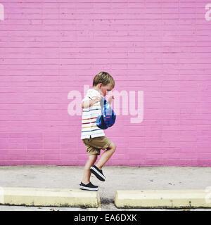 Boy walking on raised sidewalk - Stock Photo