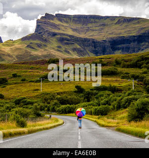 UK, Scotland, Woman with umbrella on country road - Stock Photo