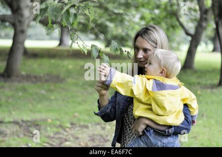 Mother and son looking at leaf - Stock Photo