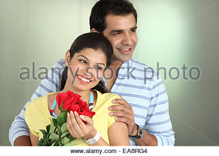 Indian young woman receiving flowers to a man - Stockfoto