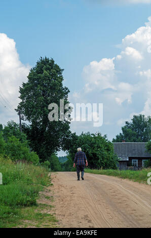 Old man on sandy road in the village. - Stock Photo