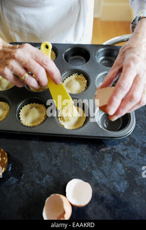 Elderly woman pensioner baking mince pies at home in her kitchen for Christmas . Egg wash to glaze the pastry - Stock Photo