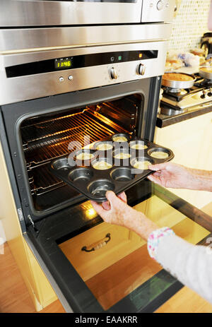 Elderly woman pensioner baking mince pies at home in her kitchen for Christmas . Putting them into the oven - Stock Photo