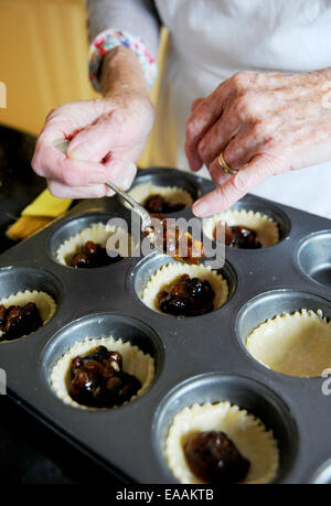 Elderly woman pensioner baking mince pies at home in her kitchen for Christmas . Putting the mincemeat into the - Stock Photo