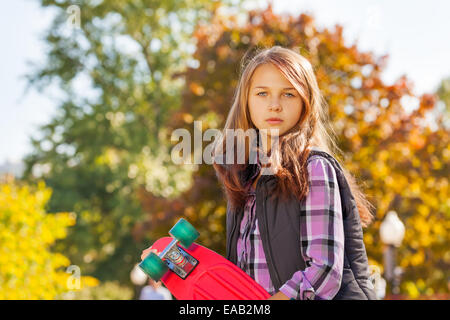 Serious looking girl holding red skateboard - Stock Photo