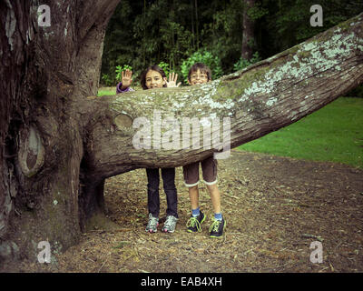 Boy and girl hide behind tree branch - Stock Photo