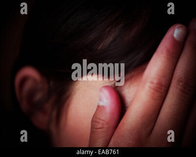 Girl hides face in hands - Stock Photo
