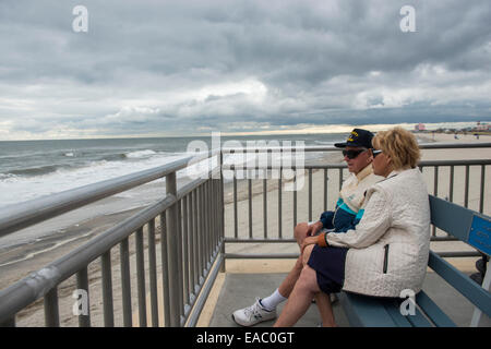 A retired couple sit on the boardwalk by the sea in Ocean City, New Jersey USA - Stock Photo