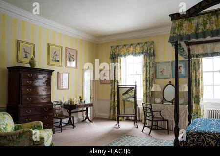 Antique wooden four poster bed with floral patterned fabrics in bedroom - Stock Photo