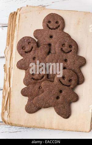 Gingerbread men on vintage cookbook - Stock Photo