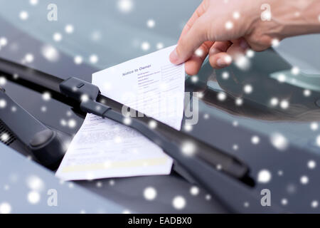 close up of male hand with parking ticket on car - Stock Photo
