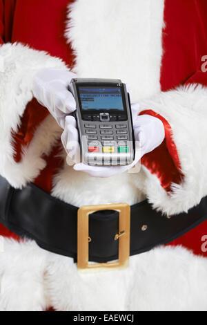 Close Up Of Santa Claus Holding Credit Card Reader - Stock Photo