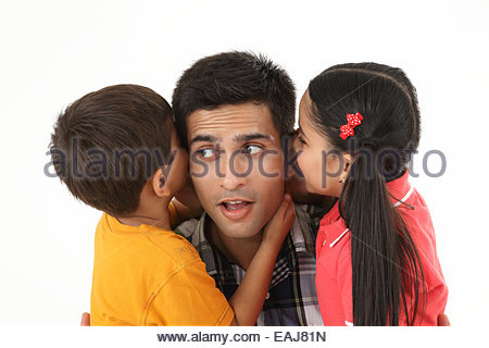 Indian boy and girl whispering into their father ear - Stockfoto