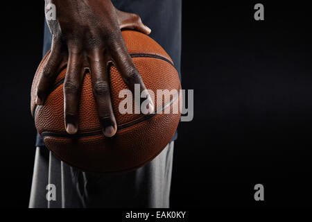 Close-up of a hand of basketball player holding a ball against black background. - Stock Photo