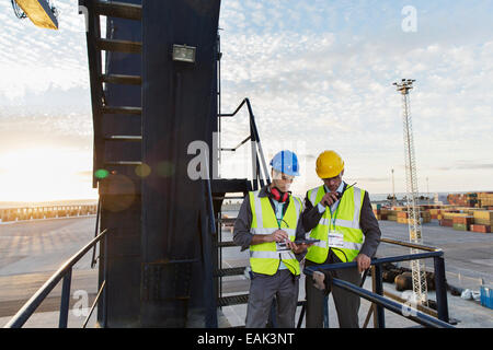 Workers using walkie-talkie on cargo crane - Stock Photo