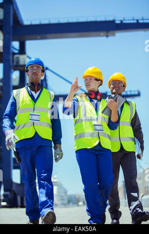 Workers and businessman talking near cargo crane - Stock Photo