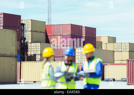 Businessman and workers talking near cargo containers - Stock Photo