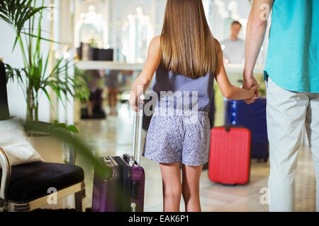 Rear view of father and daughter standing with suitcases in hotel lobby, holding hands - Stock Photo