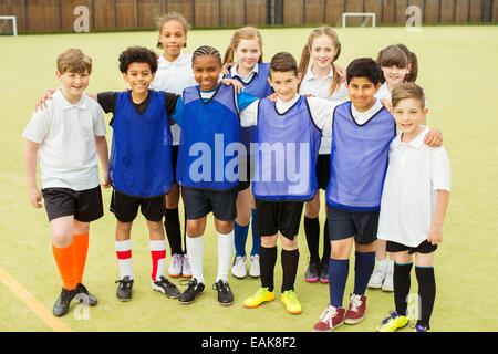 Group portrait of children wearing sport uniforms standing in school gym - Stock Photo