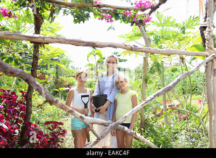 Portrait of woman and two girls standing in garden with shovel and tree seedling - Stock Photo