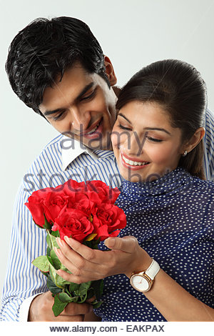 Indian man giving bunch of flowers to his girlfriend - Stockfoto