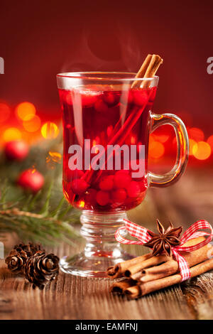 Hot mulled wine with berries, cinnamon sticks and anise - Stock Photo
