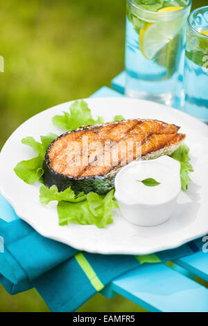 Grilled salmon steak on a fresh green salad with garlic sauce - Stock Photo
