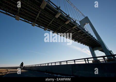bicyclist under Verrazano-Narrows Bridge - Stock Photo