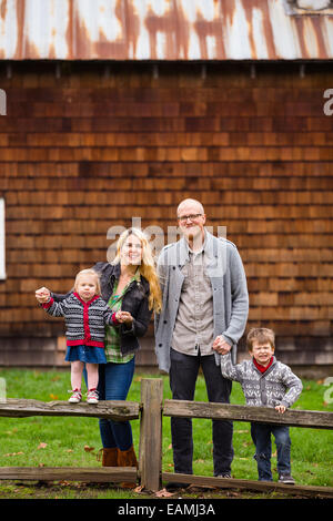 Family lifestyle portrait of a mother, father, son and daughter in front of a rustic barn in the country. - Stock Photo