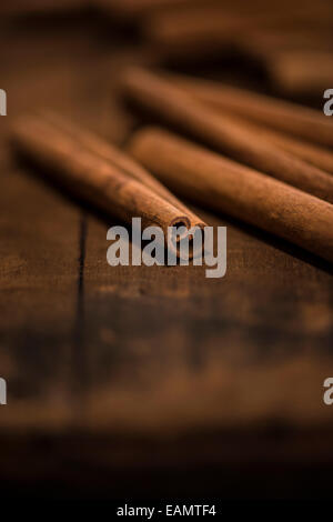 Whole cinnamon sticks on a rustic wood surface. - Stock Photo