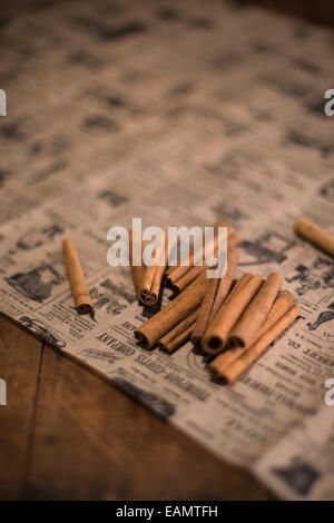 Whole cinnamon sticks on antique newspaper on a rustic wood surface. - Stock Photo